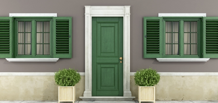 Green front door between two windows.